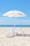 Beautiful white beach umbrella on a sunny beach. Royalty Free Stock Photos