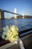 Beautiful White Bouquet and Bridge. A variety of white flowers make up this wedding bouquet with diamond and pearl accents with the bay and bridge in the Royalty Free Stock Image