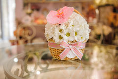 Beautiful white bouquet of mixed flowers in basket on table Stock Photo