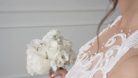 Beautiful white bridal bouquet of roses in a bright interior stock video