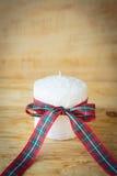 Beautiful white candle and Christmas ribbon Stock Photo