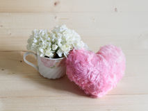 Beautiful white carnation flowers in lovely tea cup with soft pink heart on wooden background Royalty Free Stock Images