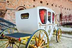 Beautiful white carved wooden royal rich carriage with large wheels decorated with gold patterns next to the old European stock photography
