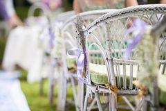 Beautiful white chairs at wedding aisle with flowers and a ribbo Royalty Free Stock Photo