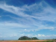 Beautiful white cloud in wide blue sky over the green mountain and field Stock Photo