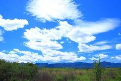 Beautiful white clouds on clear blue sky. Mountain peaks on horizon, Lika region in Croatia stock photography