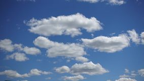 Beautiful white clouds moving fast high in the blue sky, Time-lapse. Sunny sky on a summer day.  stock footage