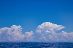 Beautiful white clouds over the sea in similar shape, kalimantan. Beautiful white clouds over the sea on a blue sky in similar shape, kalimantan, borneo island royalty free stock image