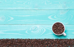 Beautiful white coffee cup with coffee beans on turquoise wooden background stock images