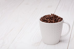 Beautiful white coffee cup with coffee beans on wooden background Stock Image