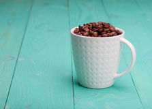 Beautiful white coffee cup with coffee beans on wooden turquoise  background Stock Photography