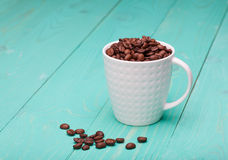 Beautiful white coffee cup with coffee beans on wooden turquoise  background Royalty Free Stock Photo