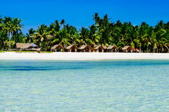 Beautiful white coral sand beach with palms and cottages, turquoise blue ocean Royalty Free Stock Image