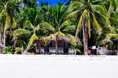 Beautiful white coral sand beach with palms and cottages, turquoise blue ocean Royalty Free Stock Photography