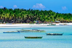Beautiful white coral sand beach with palms and fishing boats, turquoise blue ocean Royalty Free Stock Photo