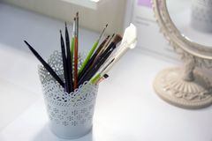 A beautiful, white cup with openwork patterns for storing brushes for make up royalty free stock photos