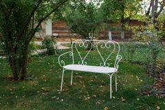 Beautiful white decorative bench in the garden stock image