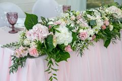 Free Beautiful White Dinner Table For Newlyweds Decorated With Greenery And Long Cloth. Long Flower Arrangement Of Hydrangeas, Roses, G Royalty Free Stock Images - 130587809