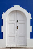Beautiful white door on a blue wall Royalty Free Stock Images