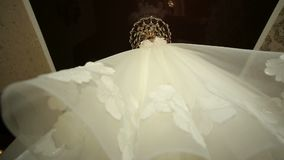 Beautiful wedding dress hung on the chandelier. stock video