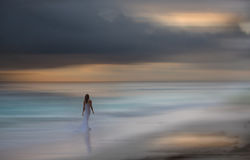 Beautiful white dressed woman walks at the beach. Blurred background. Stock Image