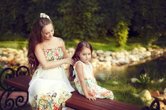 Beautiful white European woman combing long hair of his daughter stock photos