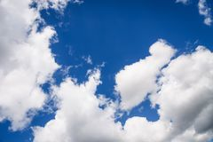Beautiful white fluffy clouds on a blue sky background, copy space. Beautiful white fluffy clouds on a deep blue sky background. Scenic sky, copy space stock image