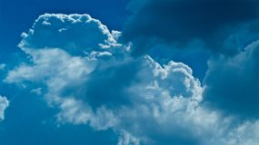 Beautiful white fluffy clouds in blue sky. Beautiful white fluffy clouds formation in a amazing blue sky background and clouds are backlit in sunshine stock images
