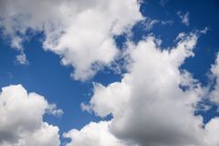 Beautiful white fluffy clouds on a blue sky background. Beautiful white fluffy clouds on a deep blue sky background. Scenic sky stock image