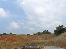 Beautiful white fluffy clouds on vivid blue sky above brown land at infrastructure on ground,  construction site area in a suny stock images