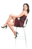 Beautiful white girl in dress on stool stock images
