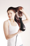 Beautiful white girl drying her hair with a hairdr Royalty Free Stock Photo