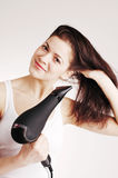 Beautiful white girl drying her hair with a hairdr Stock Photos