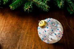 Beautiful white glass ball and green spruce branch on wooden bac. Kground. Christmas, new year`s card. Copy space royalty free stock photo