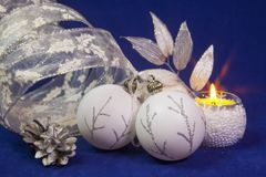 Beautiful white glass New Year`s balls with a silver pattern, white brilliant tinsel, cone on a blue background - New Year`s compo. Sition, a card Stock Photo