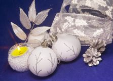 Beautiful white glass New Year`s balls with a silver pattern, white brilliant tinsel, cone a on a blue background - New Year`s com. Position, a card Royalty Free Stock Image