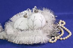 Beautiful white glass New Year`s balls with a silver pattern, white brilliant tinsel, cone and a pearl beads on a blue background. New Year`s composition, a Stock Photo