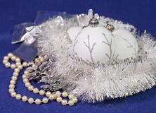 Beautiful white glass New Year`s balls with a silver pattern, white brilliant tinsel, cone and a pearl beads on a blue background. New Year`s composition, a Stock Photography