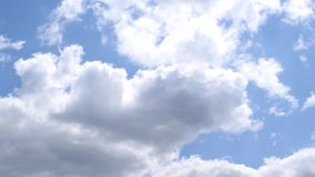 Beautiful white and grey cumulus clouds moving quickly on background of blue sky stock footage