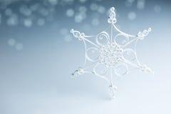 Beautiful white handmade quilling snowflake on blue - horizontal Stock Photo