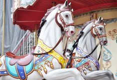 Beautiful white horses Christmas carousel in a holiday park. Two horses on a traditional fairground vintage Paris carousel. Merry-. Beautiful white horses stock image