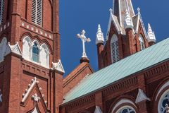 Beautiful white iron cross on a Gothic Revival church. Horizontal aspect stock photo
