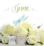 Beautiful white June Bride theme cupcake with seasonal flowers and decorations for the month of June. With sample text or copy space for your text here Stock Images