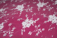Beautiful white lace flowers on a pink background. White lace flowers embroidered on mesh textile, pink fabric background Stock Photos