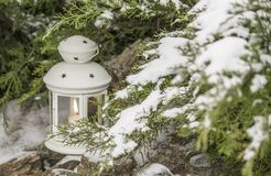 Beautiful white lantern in the snow. Candle in the snow on a background/ stock photography
