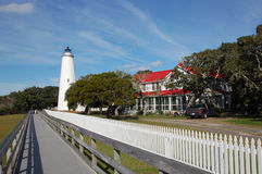Beautiful white lighthouse, old oaks and a blue blue sky on the NC Island of Ocracoke. On a sunny day, the Ocracoke lighthouse stands majestically among gnarled stock photography