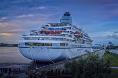 Beautiful white cruise ship on stay at Riga harbor during sunset Royalty Free Stock Photography