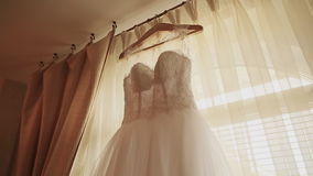 Beautiful white luxury wedding dress on hanger on the background of a window stock video