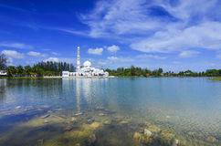 Beautiful white mosque with reflection in the lake during clean blue sky Stock Image