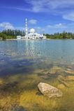 Beautiful white mosque with reflection in the lake during clean blue sky Stock Images